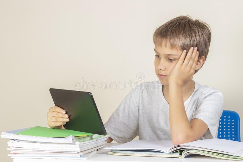 坐在与书笔记本的桌上和使用片剂计算机的孩子 库存图片