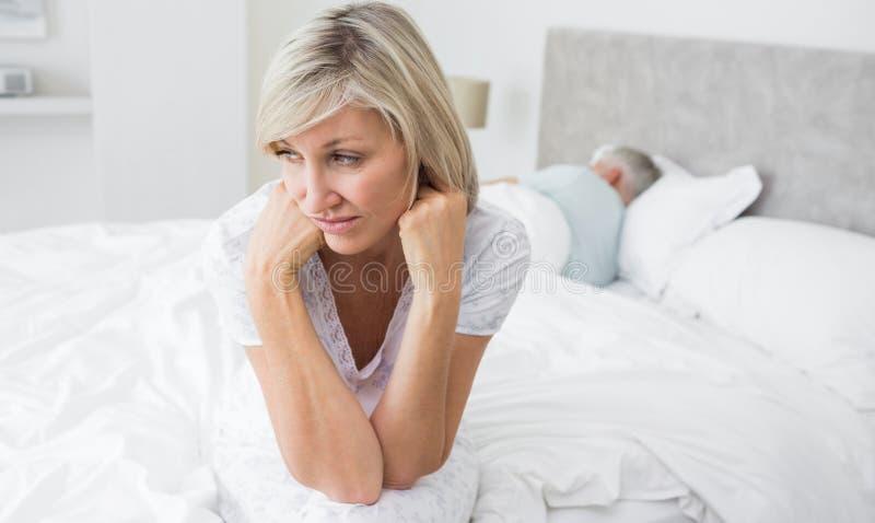 坐在与人的床上的被拉紧的成熟妇女在背景中 库存照片