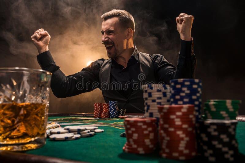 坐在与卡片和芯片的啤牌桌后的年轻英俊的人 免版税图库摄影