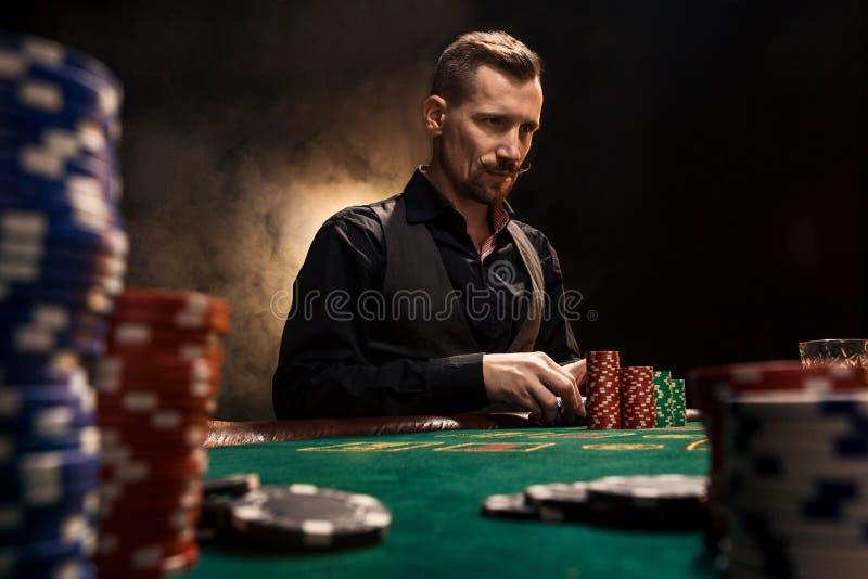 坐在与卡片和芯片的啤牌桌后的年轻英俊的人 免版税库存照片