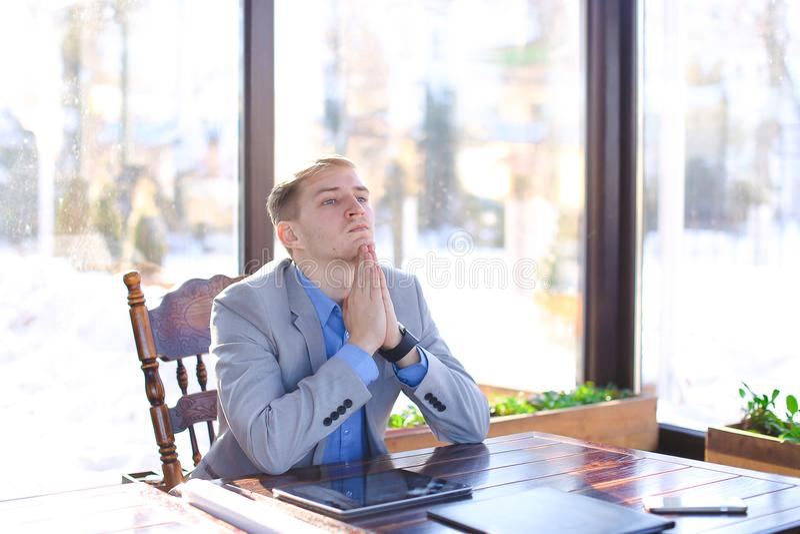 坐在与卷轴式记录纸, smartphon的咖啡馆的疲乏的年轻教授 库存图片
