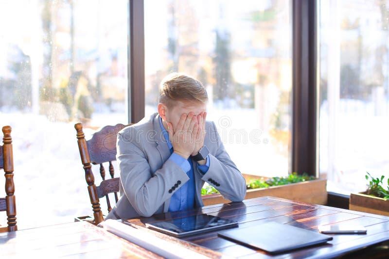 坐在与卷轴式记录纸, smartphon的咖啡馆的疲乏的年轻教授 免版税库存照片