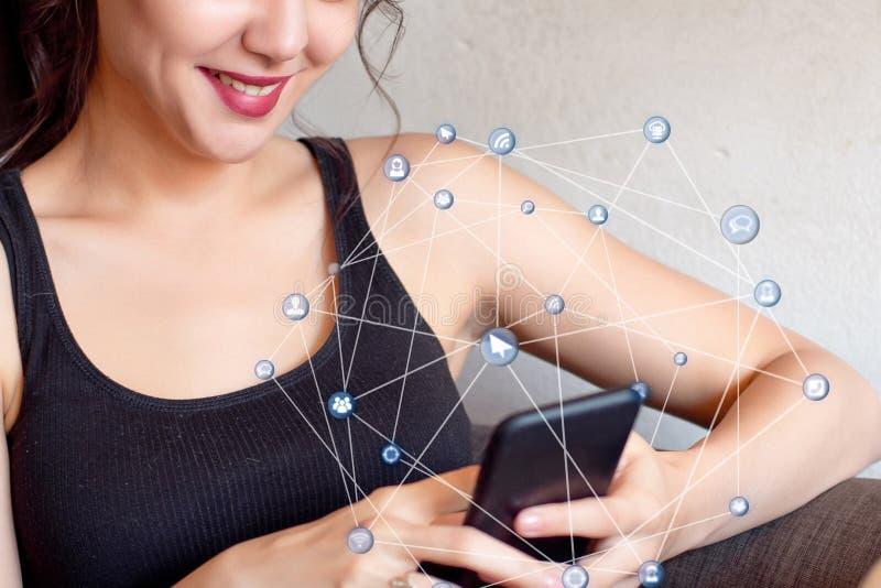 坐在与咖啡的桌上的妇女使用她的智能手机 库存照片