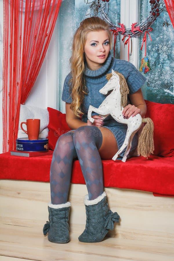 坐在与圣诞节decorat的窗口附近的白肤金发的少妇 免版税库存图片