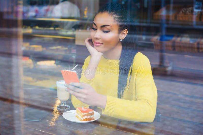 坐在与她的拿铁饮料的一家咖啡店的混合的族种妇女 免版税图库摄影