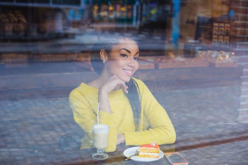坐在与她的拿铁饮料的一家咖啡店的混合的族种妇女 库存图片