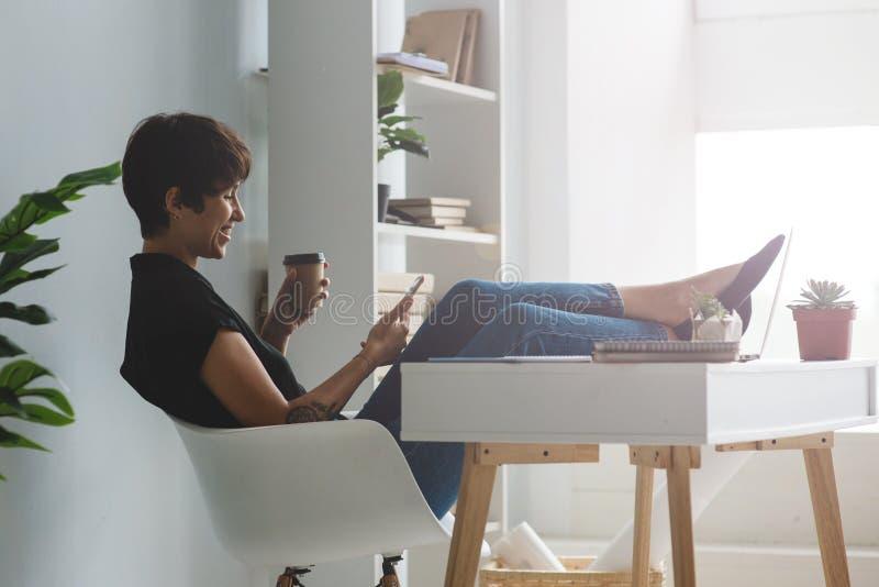 坐在与她的智能手机的一把椅子的俏丽的年轻女实业家有在书桌的腿的 免版税图库摄影