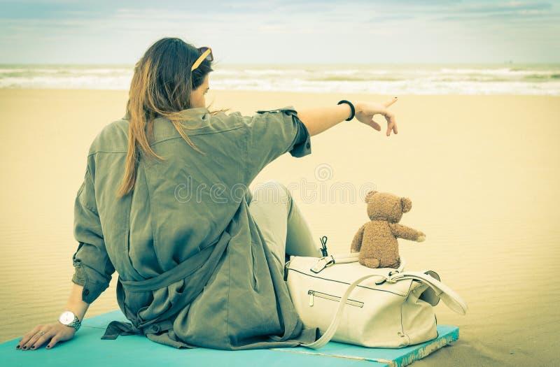 坐在与她的玩具熊的海滩的年轻单身妇女 库存照片