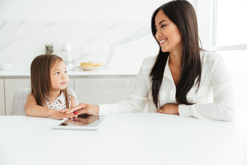 坐在与小逗人喜爱的女孩的桌上的愉快的妈妈 免版税库存照片