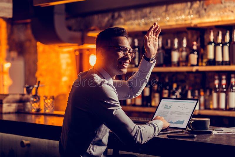 坐在与挥动他的朋友的膝上型计算机的酒吧停留演出地的自由职业者 库存图片