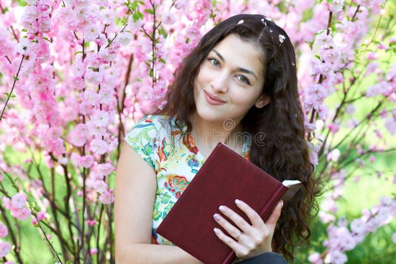 坐在与桃红色花的灌木附近和读书的女孩画象 库存照片