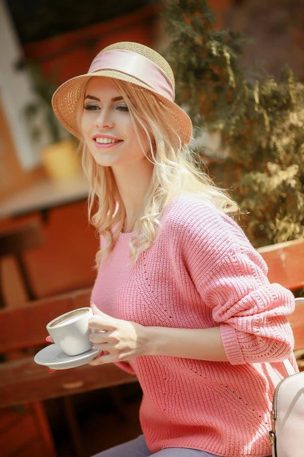 坐在与片剂和一杯的一个咖啡馆的一件桃红色礼服的美女热奶咖啡 使用片剂的年轻愉快的妇女 库存图片