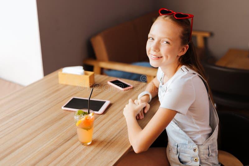 坐在与片剂和电话的桌附近的放光的现代少年 免版税图库摄影