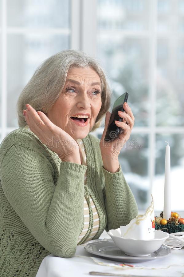 坐在与电话的桌上的妇女 免版税库存图片