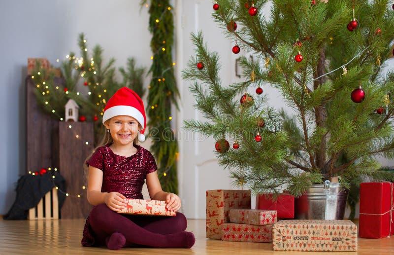 坐在与礼物的圣诞树附近的女孩在她的手上 库存图片