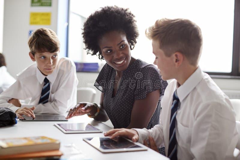 坐在与穿制服的学生的表上的女子高中学校教师使用在教训的数字片剂 免版税图库摄影