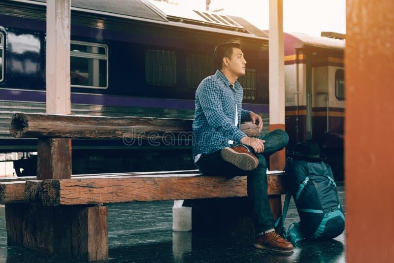 坐在与等候火车` s arr的火车站的年轻人 免版税库存图片