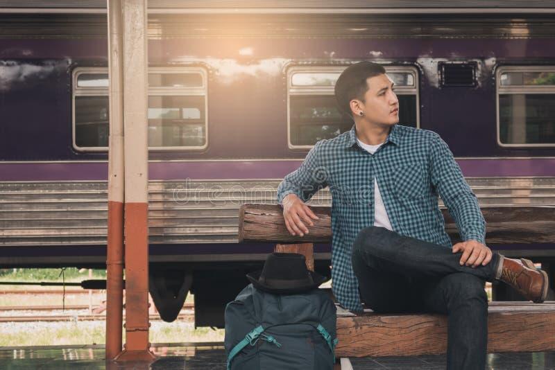 坐在与等候火车` s arr的火车站的年轻人 库存照片