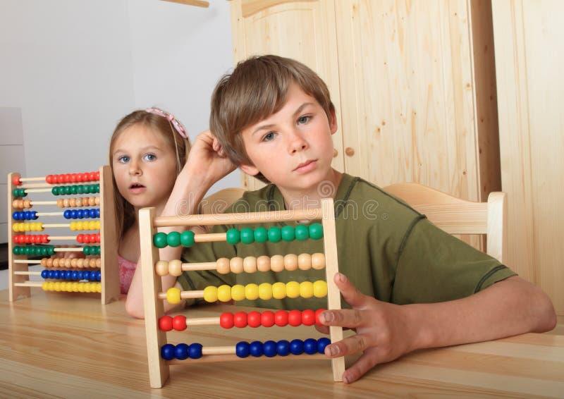 坐在与算盘的木桌后的孩子 免版税库存照片