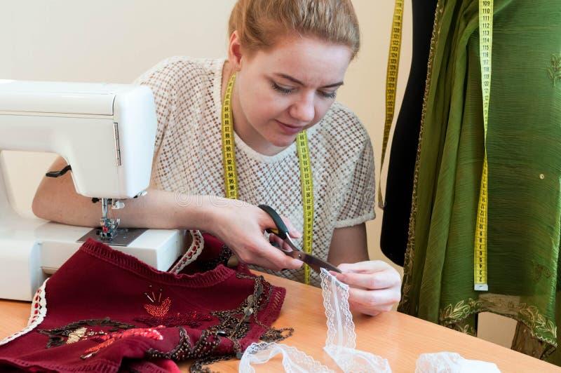 坐在与缝纫机的桌上和切开白色鞋带的裁缝 库存图片