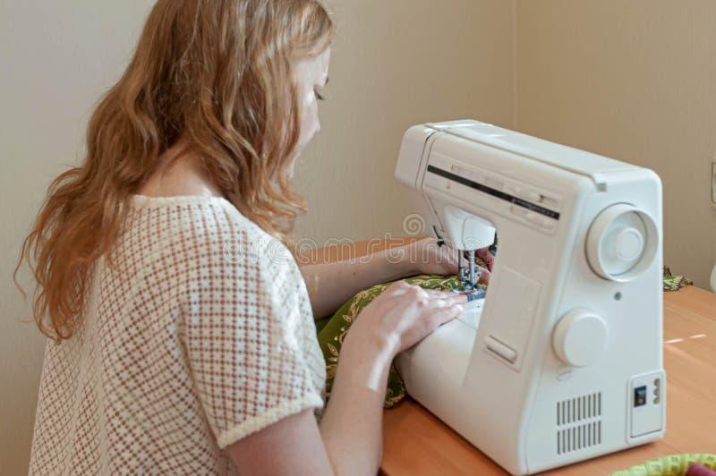 坐在与缝纫机的桌上的裁缝 免版税库存图片