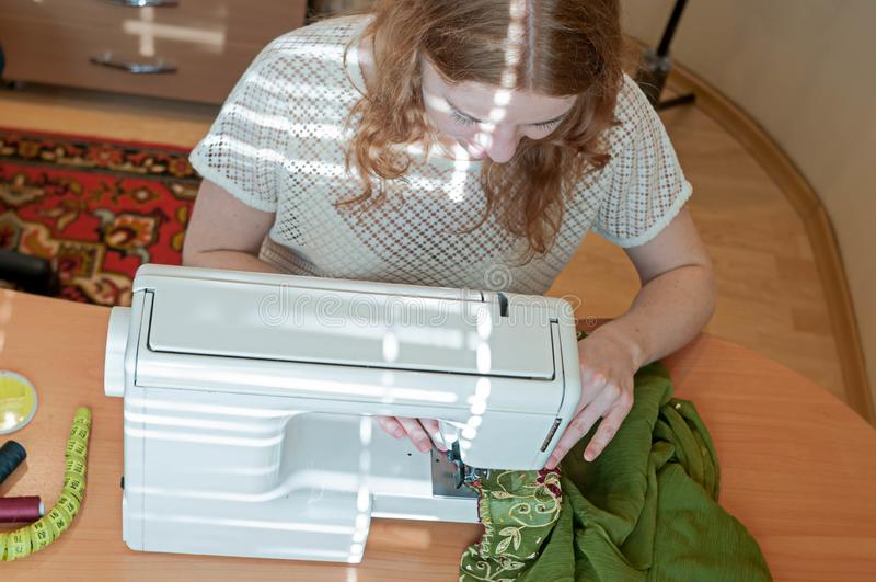 坐在与缝纫机,绿色布料的桌上的裁缝 免版税库存图片