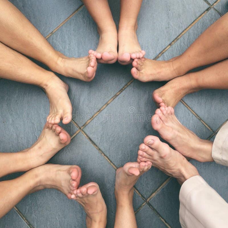 坐在与脚接触的一个圈子的人们 库存照片
