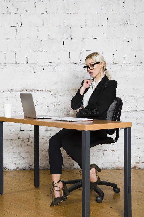 坐在与膝上型计算机、笔记本和玻璃的一张办公室桌上的年轻白肤金发的秀丽女实业家在衣服 到达天空的企业概念金黄回归键所有权 库存照片
