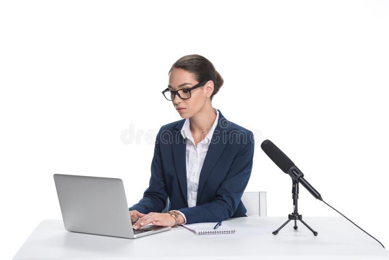 坐在与膝上型计算机、笔记薄和话筒的桌上的可爱的女性新闻广播员, 免版税图库摄影