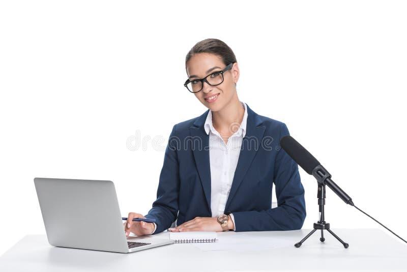 坐在与膝上型计算机、笔记薄和话筒的桌上的可爱的微笑的女性新闻广播员, 库存照片