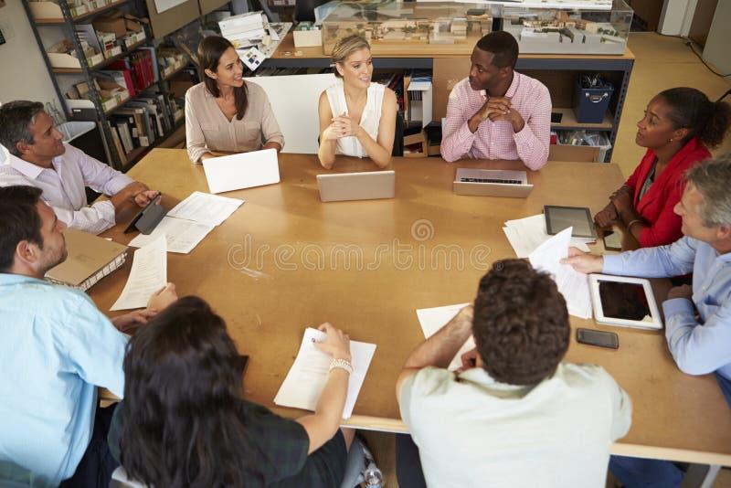坐在与膝上型计算机和片剂的表会议上的建筑师 库存图片