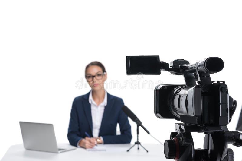 坐在与膝上型计算机和话筒的桌上和看照相机的女性新闻广播员, 免版税库存图片