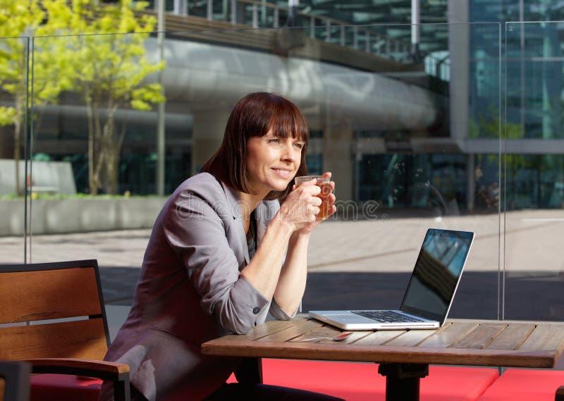 坐在与膝上型计算机的室外咖啡馆的女实业家 免版税库存图片