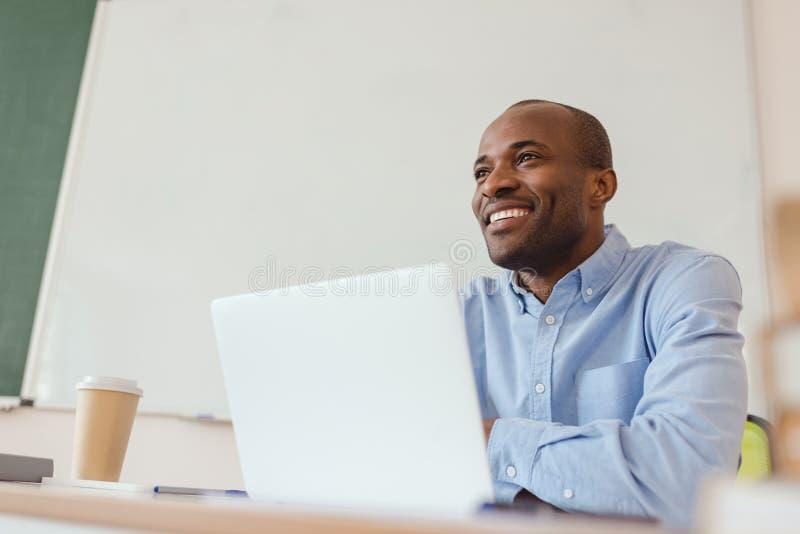 坐在与膝上型计算机的桌上的低角度观点的微笑的非裔美国人的老师 库存照片