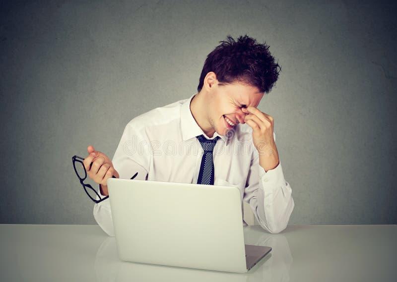 坐在与膝上型计算机的桌上的疲乏的商人摩擦眼睛 免版税库存图片