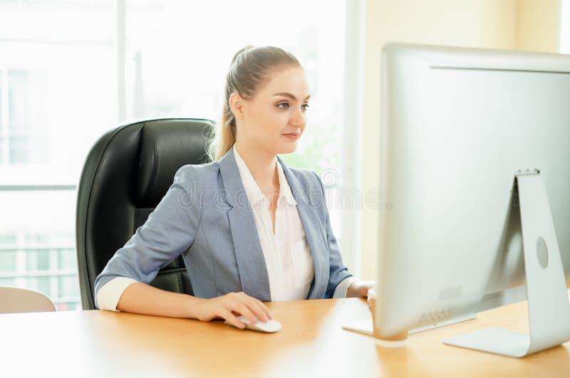 坐在与膝上型计算机的桌上的美丽的企业夫人在offi 库存照片