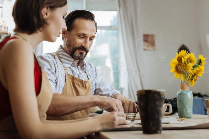 坐在与花瓶的桌上的陶瓷技师夫妇用向日葵 免版税库存照片