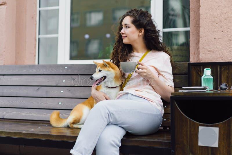 坐在与茶的街道咖啡馆的俏丽的女孩和shiba inu狗微笑 图库摄影