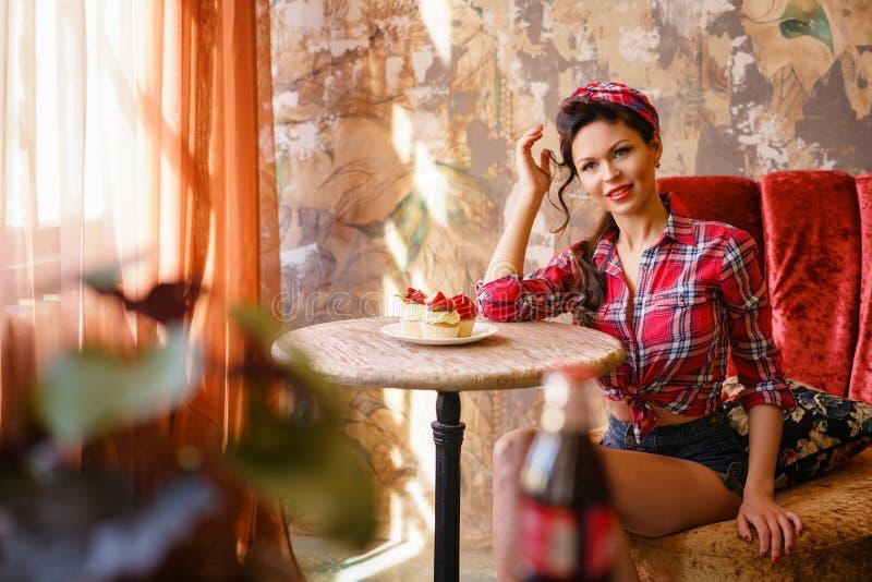 坐在与蛋糕的一张桌,别针上的咖啡馆的一年轻女人 免版税库存照片