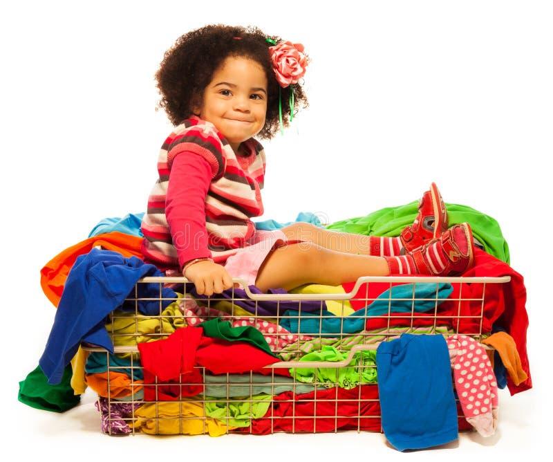 坐在与衣裳的篮子的黑人女孩 库存照片