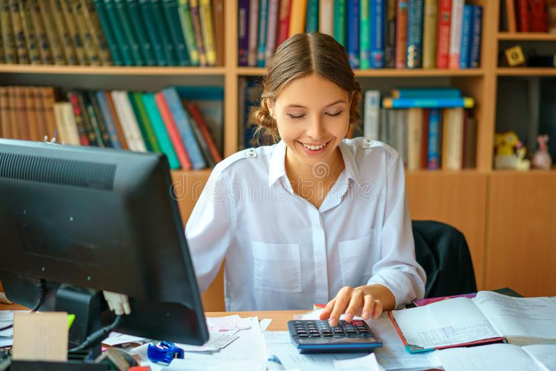 坐在与计算机和纸工作环境的桌上的白色衬衫的年轻愉快的企业夫人 免版税库存照片