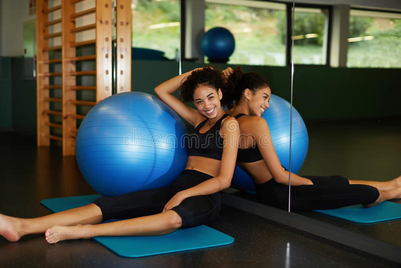 坐在与适合球的健身房的愉快和美丽的少妇 免版税库存图片