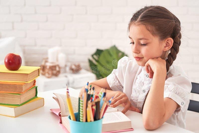 坐在与铅笔和课本的桌上的快乐的女孩 做家庭作业的愉快的儿童学生在桌上 ?? 库存照片