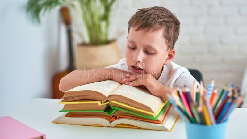 坐在与铅笔和课本的桌上的快乐的小男孩 做家庭作业的愉快的儿童学生在桌上 库存照片