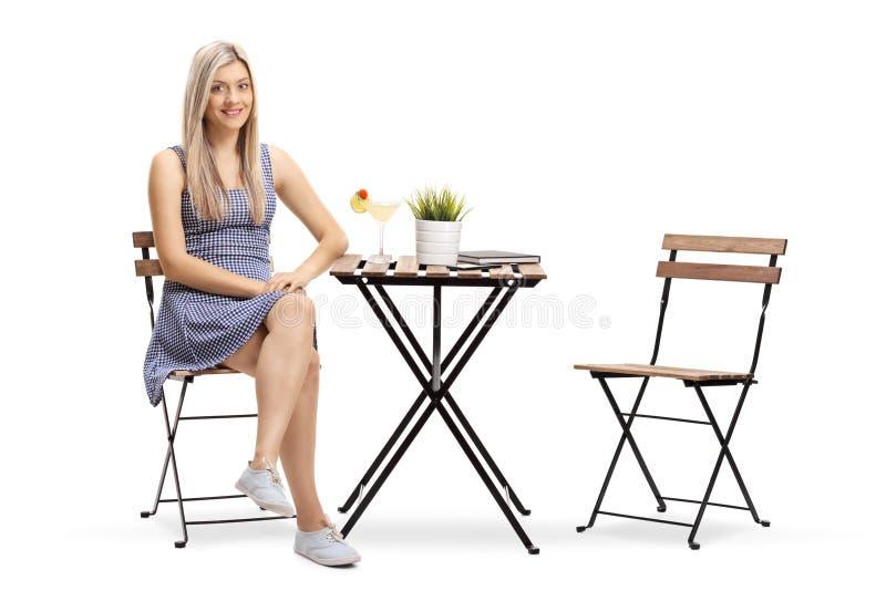 坐在与鸡尾酒的一个咖啡馆和看的年轻女人 免版税库存图片