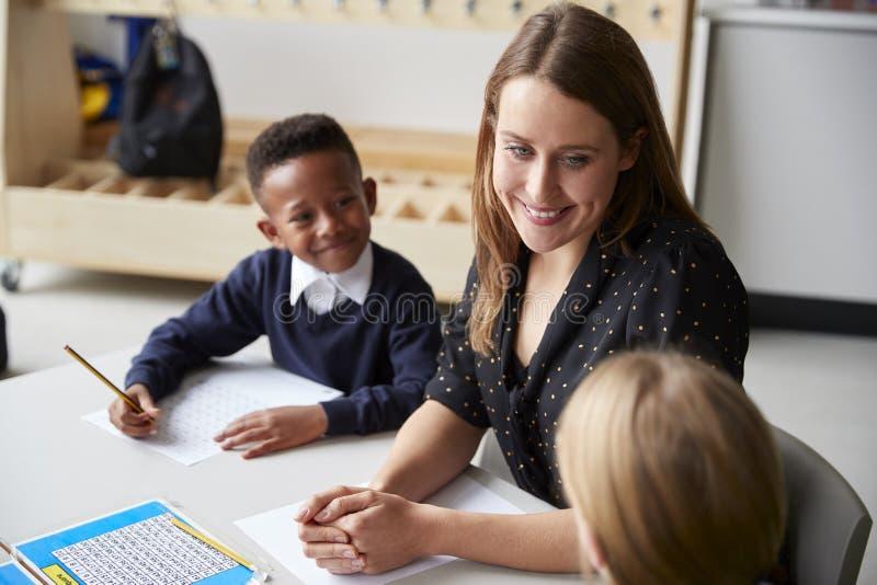 坐在两个学校孩子之间的被举起的观点的一女性主要学校老师在桌上在教室,微笑对彼此du 免版税库存图片
