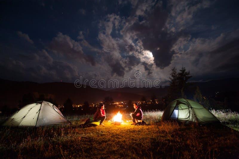 坐在两个帐篷附近的男人和妇女夜 免版税库存照片