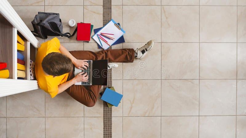 坐在书架和使用膝上型计算机的年轻男生 免版税图库摄影