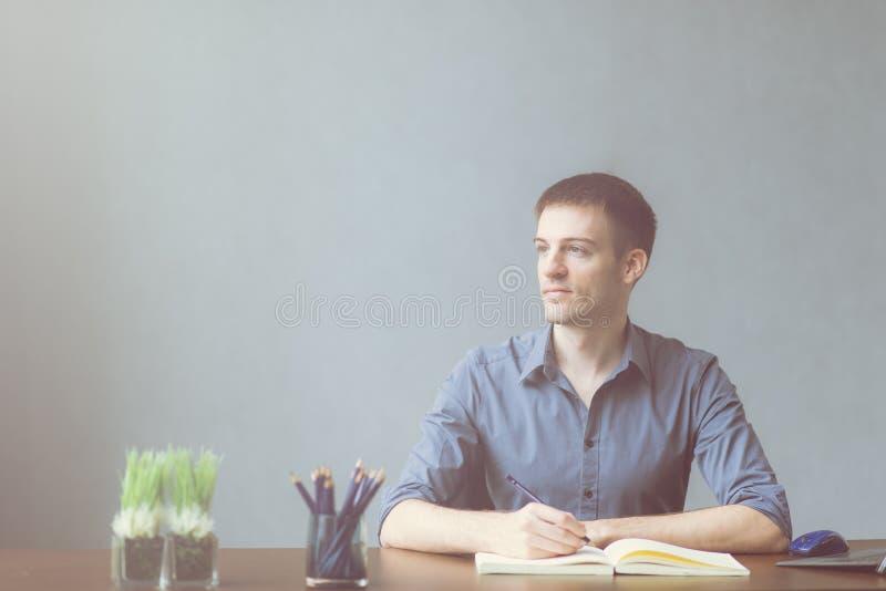 坐在书桌办公室桌上和采取在笔记本的年轻商人白种人笔记 写和看窗口 图库摄影