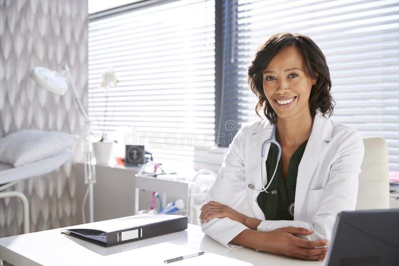 坐在书桌后的微笑的女性Wearing White Coat With医生听诊器画象在办公室 库存照片